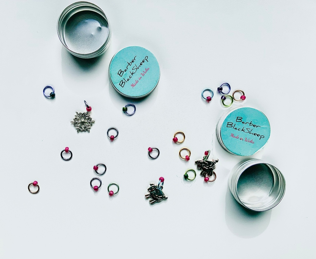 Image shows two tins of scattered metal ring stitch markers