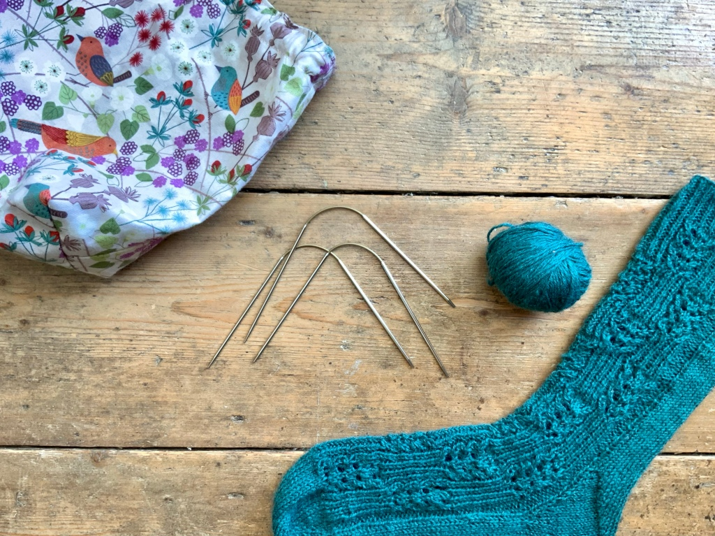 Image shows Addi cabled double pointed needles for sock knitting. Image also show sock in progress.