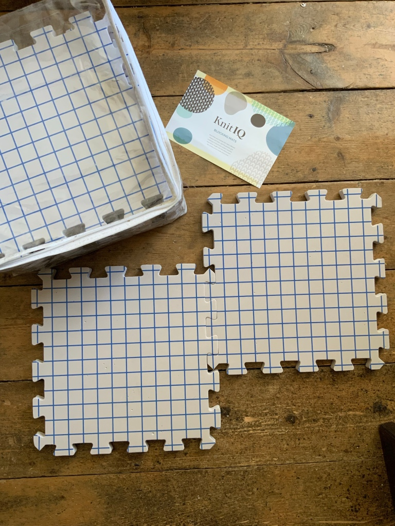 Image shows two interlocking knitting blocking mats with grid pattern on front and storage case