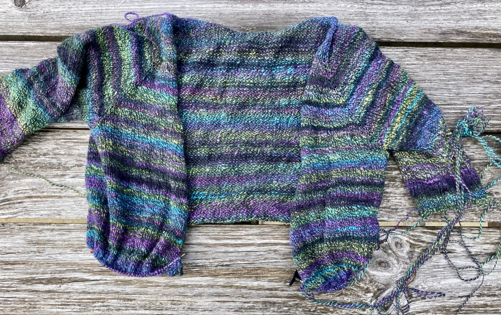 Image shows a partially knitted jumper