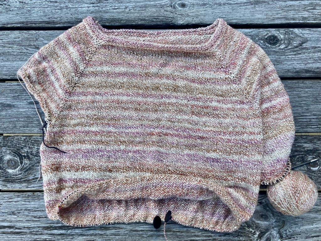 Image shows sweater in progress with half a body and half of one sleeve complete. Yarn in shades of pale pinks, brown, and white.