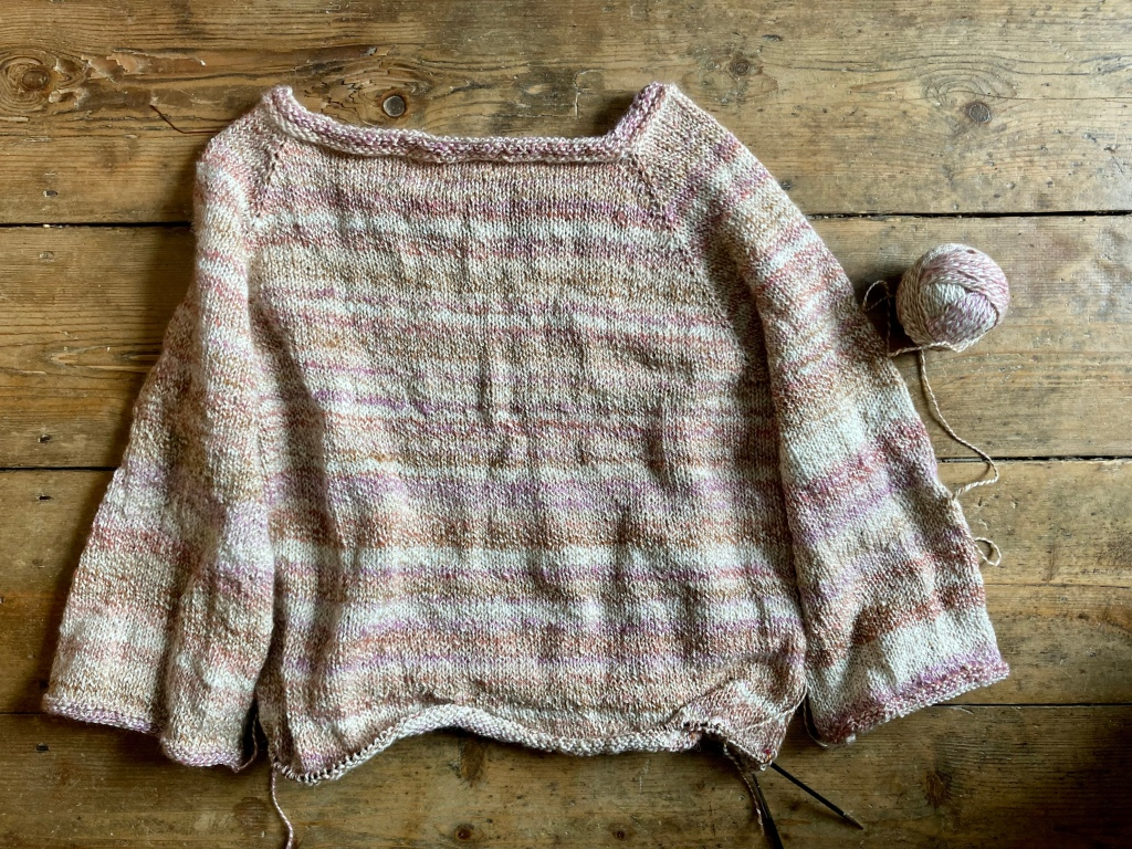 Image shows jumper knitted top down with three quarter sleeves and an incomplete body.