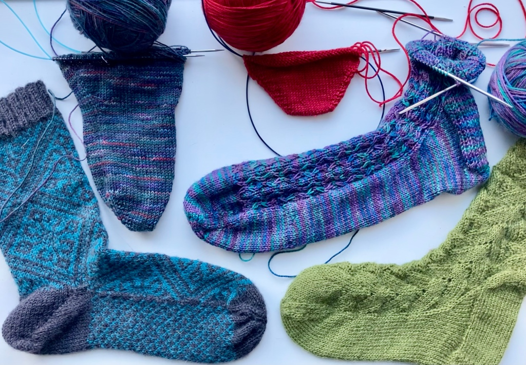Image shows five knitted socks in various stages of completeness.